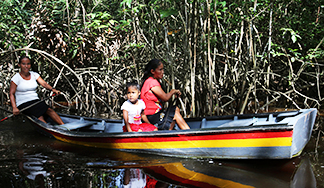 Villagers paddle along a branch of the Pomeroon River in the interior of Guyana. The Catholic Church supports scientists' efforts to study the causes and effects of climate change and insist governments, businesses get serious about protecting the environment.
