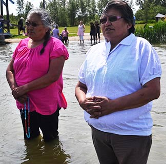 Lac Ste. Anne pilgrims Genevieve Besskkaystare and her sister Jeanette Tsannie of Wollaston Lake, Sask., prayed in the sacred waters of the lake on July 20.