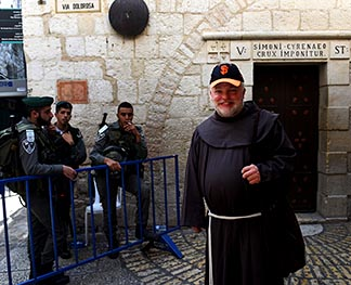Brother Mark McPherson walks by the fifth station of the cross as Israeli border police stand guard near a site of recent stabbings.