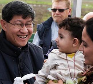 Cardinal Luis Antonio Tagle gives a food bag to a refugee family as they arrive at a transit camp in Idomeni, Greece, on the border of Macedonia. Thousands of refugees are arriving in Greece from Syria, Afghanistan, Iraq and other countries and then traveling further into Europe.