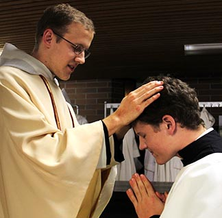 Fr. Caesarius Marple blesses his brother, Luke Marple, who was an altar server at the Mass.