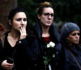 People react as they look at the Bataclan music hall in Paris Nov. 16, the site of one of the terrorist attacks that killed 129 people in the city and 43 in Beirut, Lebanon.