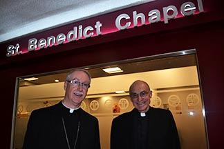 Archbishop Richard Smith and Fr. Oscar Monroy stand in front of the new location of St. Benedict's Chapel in Edmonton's City Centre Mall.