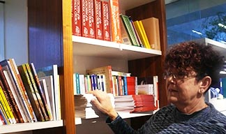 Manager Shirley Kulmatycki scans some of the packed shelves in the Newman Theological College Bookstore.