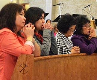 Worshipers bow their heads in prayer during the first Mass at Corpus Christi Church Jan. 31.