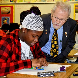 Student Ava Alexis-Seggumba works under the watchful eye of CCODP volunteer Martin Blanchet.