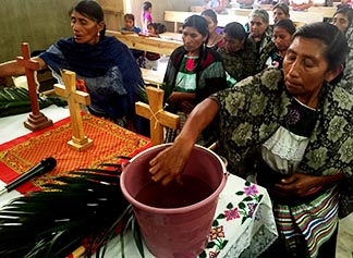 Indigenous women dip their hands in holy water during a Jan. 21 service in Mexico's southern Chiapas state.