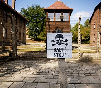 A guard tower is seen beyond an area enclosed with barbed wire at Auschwitz-Birkenau Memorial and State Museum in Oswiecim, Poland.