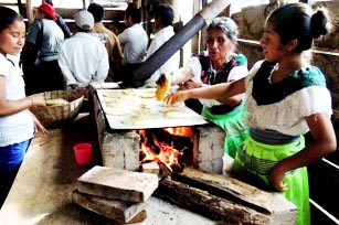 Ti'Akil women cook tortillas on community ovens.