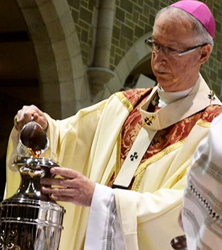 Archbishop Smith pours balsam into olive oil to make the holy oil of Chrism.
