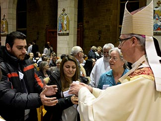 Hanna Shandi and Nash Shakkour, recently arrived Syrian refugees, receive the holy oils for St. Matthew Parish in Rocky Mountain House from Archbishop Richard Smith following the Chrism Mass March 21 at St. Joseph's Basilica.