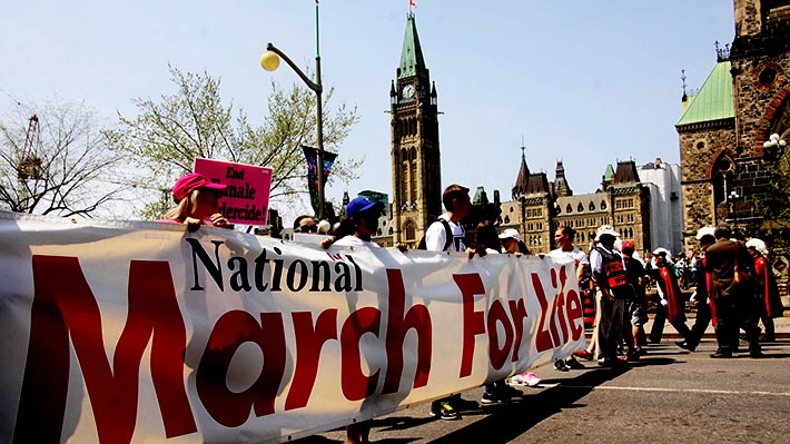 Pro-life supporters carry a banner during the annual National March for Life on Parliament Hill May 12 in Ottawa.