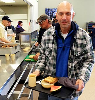 Bishop Donald Bolen of Saskatoon picks up breakfast June 18, after spending a night in a city park as part of a homelessness challenge.