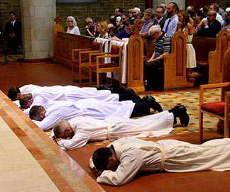 The five diaconal candidates lie prostrate before the altar prior to their ordinations July 9 at St. Joseph's Basilica in Edmonton.