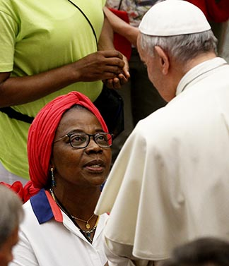 Pope Francis greets a woman during a July 6 audience with 200 people from Lyon, France, who are living in difficult or precarious situations.
