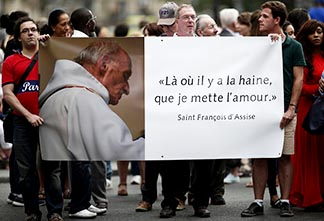 People hold a banner with a picture of French priest Fr. Jacques Hamel, which reads Where there is hatred, let me sow love