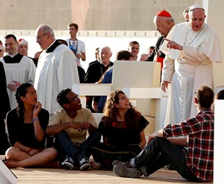 Pope Francis gestures after inviting World Youth Day pilgrims to sit in front of his chair during the July 30 prayer vigil in Kraków, Poland.