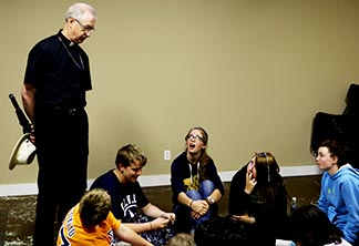 Archbishop Richard Smith drops in to visit some campers during a soggy day at Our Lady of Victory Camp.